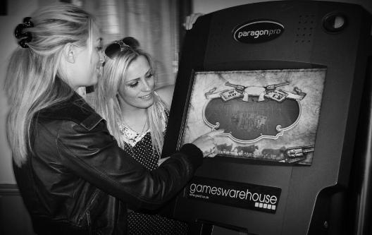 Two women playing a pub quiz machine